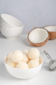 Kokos biologische zoete veganistische truffels met vulling kwark geserveerd in kom op witte houten tafel