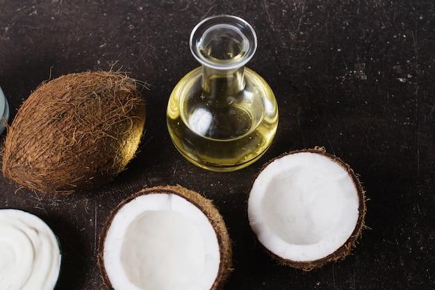 Kokos en kokosolie op een donkere marmeren achtergrond. exotische grote walnoot. persoonlijke verzorging. spa behandelingen