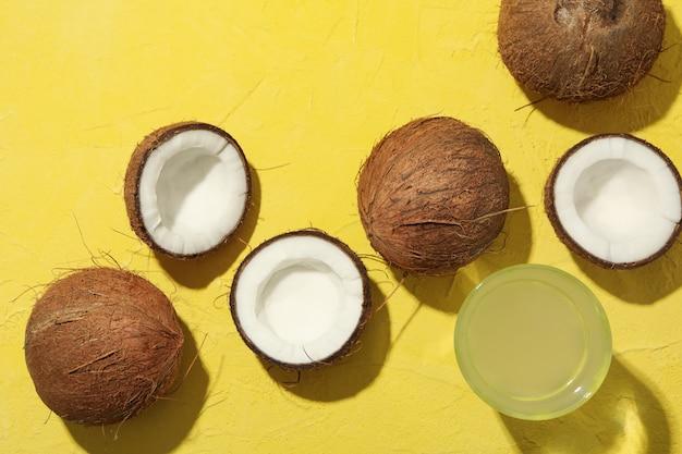 Kokos en water op gele tafel, bovenaanzicht. tropisch fruit