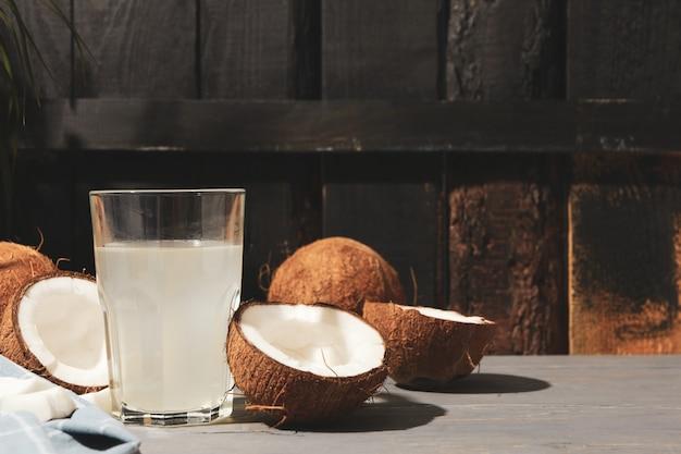 Kokos en water op hout, ruimte voor tekst. tropisch fruit