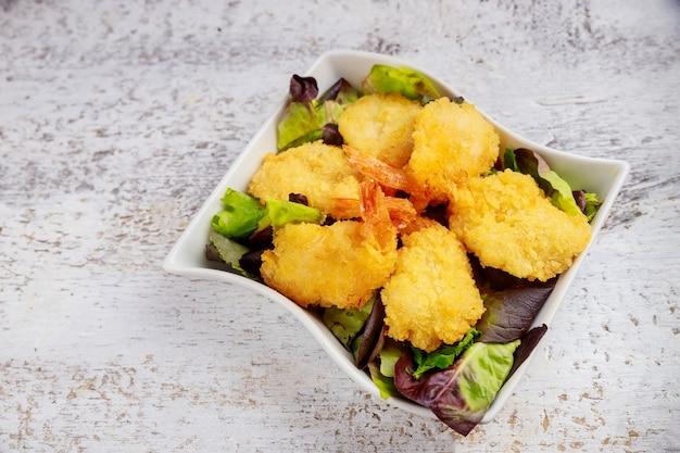 Kokos gepaneerde garnalen in kom met salade witte oppervlak.