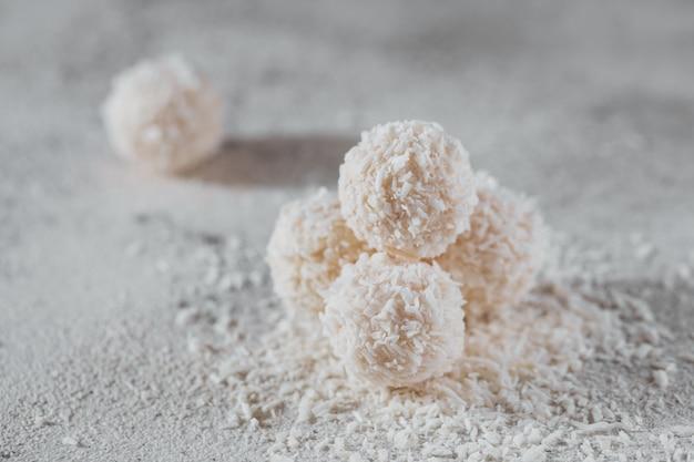 Kokos gezonde suikervrije ballen in kokosvlokken op lichtgrijze witte achtergrond