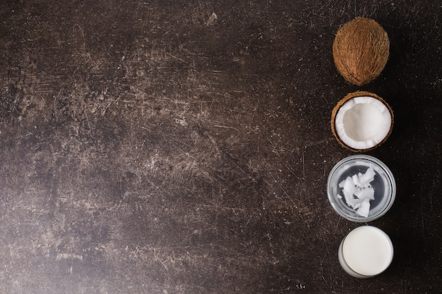 Kokos, room, kokosmelk en boter op een donkere marmeren achtergrond. exotische grote walnoot. persoonlijke verzorging. spa behandelingen