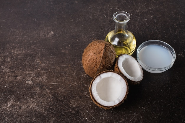 Kokos, room, kokosmelk en olie op een donkere marmeren achtergrond. exotische grote walnoot. persoonlijke verzorging. spa behandelingen