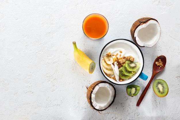Kokos yoghurt vruchten met granola geserveerd. probiotisch voedselconcept. lekker en gezond ontbijt