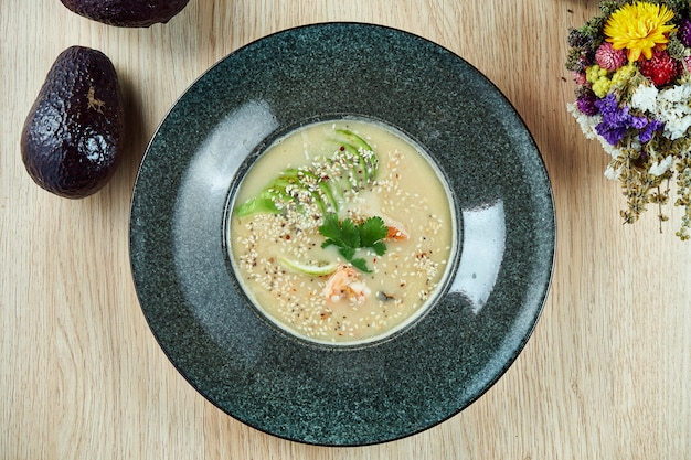 Kokos zeevruchtensoep. thaise soep met kokosmelk, limoen, garnalen en sesamzaadjes. pittig eten voor de lunch. bovenaanzicht eten plat lag