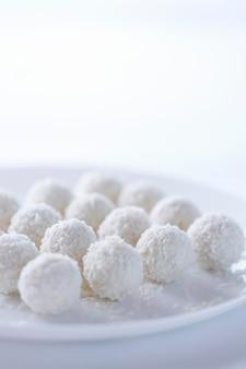 Kokoscakes licht dessert in de vorm van ballen op een lichte achtergrond