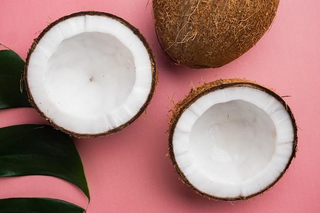 Kokoshelften, kokosstukjes set, op roze getextureerde zomerachtergrond