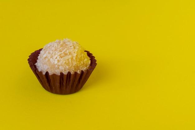 Kokosjam en gecondenseerde melk. braziliaanse traditionele zoete geïsoleerd op gele achtergrond.