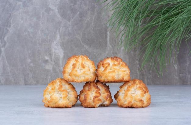Kokosmakarons op marmeren achtergrond met pijnboomtak. hoge kwaliteit foto