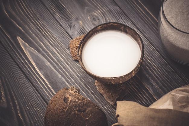 Kokosmelk op een houten achtergrond. kokos en kokosmelk. verse kokosmelk