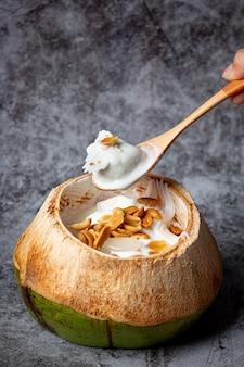 Kokosmelkijs in de kokosnoot op het donkere oppervlak