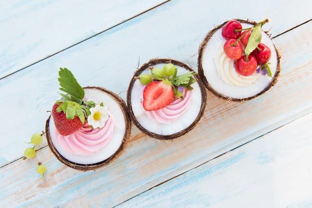 Kokosnoot cupcakes met bloemen, aardbeien en kaasroom