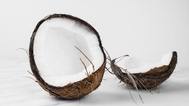 Kokosnoot die in de twee helften tegen witte achtergrond wordt verdeeld