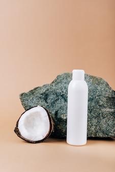 Kokosnoot en een tube cosmetica op een stenen achtergrond