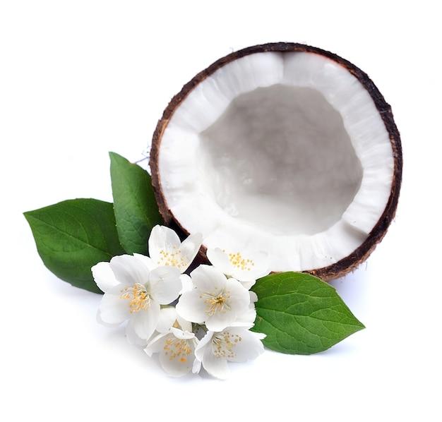 Kokosnoot en witte jasmijnbloemen op wit.