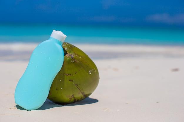 Kokosnoot en zonnebrandcrème op wit zand