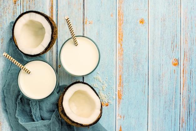 Kokosnoot, glas kokosmelk en kom met kokosvlokken op een blauw hout. bovenaanzicht.