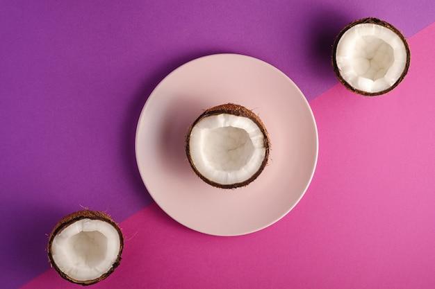 Kokosnoot half in roze plaat met nootvruchten op violette en purpere duidelijke achtergrond, abstract voedsel tropisch concept, hoogste mening