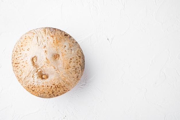 Kokosnoot hele set, op witte stenen tafel achtergrond, bovenaanzicht plat lag, met kopieerruimte voor tekst