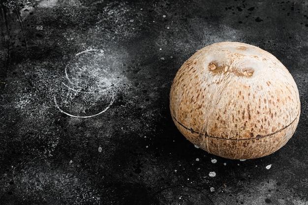 Kokosnoot hele set, op zwarte donkere stenen tafel achtergrond, met kopie ruimte voor tekst