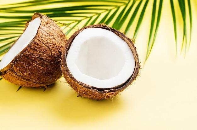 Kokosnoot helften en bladeren op gele achtergrond