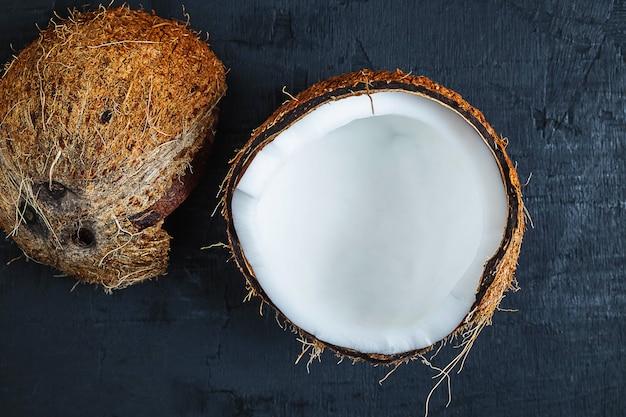 Kokosnoot in tweeën gesneden op een zwarte achtergrond