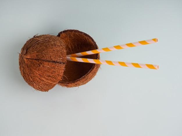 Kokosnoot met een het drinken buis op een lichtblauwe achtergrond, close-up, concept, copyspace. gesneden kokosnoot met twee buizen, kokosmelksap