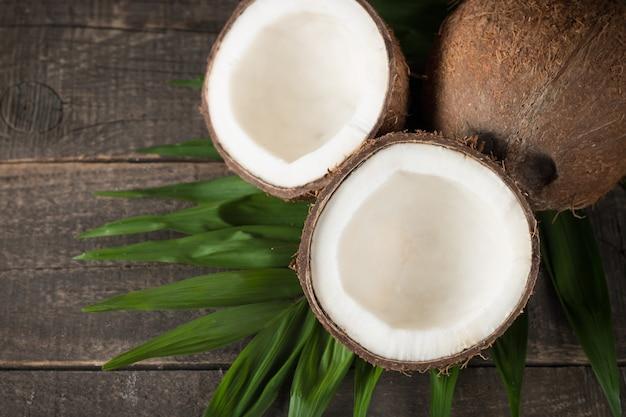 Kokosnoot met groene bladeren op een houten achtergrond.