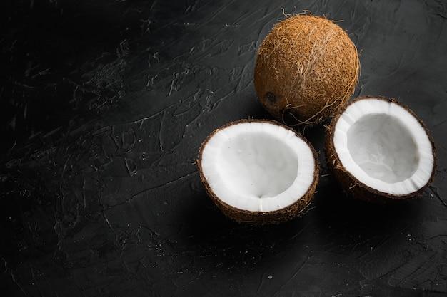 Kokosnoot met halve set, op zwarte donkere stenen tafelachtergrond, met kopieerruimte voor tekst