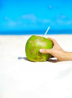 Kokosnoot met hand op wit strand