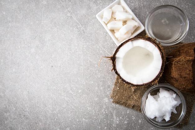 Kokosnoot met kokosnotenolie in kruik op houten achtergrond