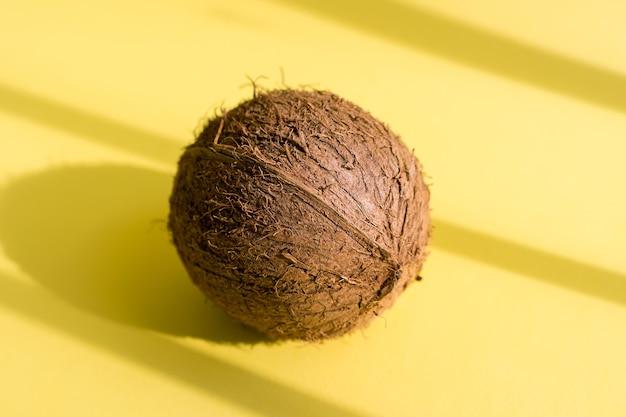 Kokosnoot met schaduwen op gele achtergrond. tropisch zomerontwerp. creatief concept.