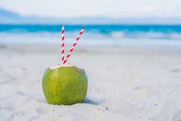 Kokosnoot met stro in het zand op het strand.