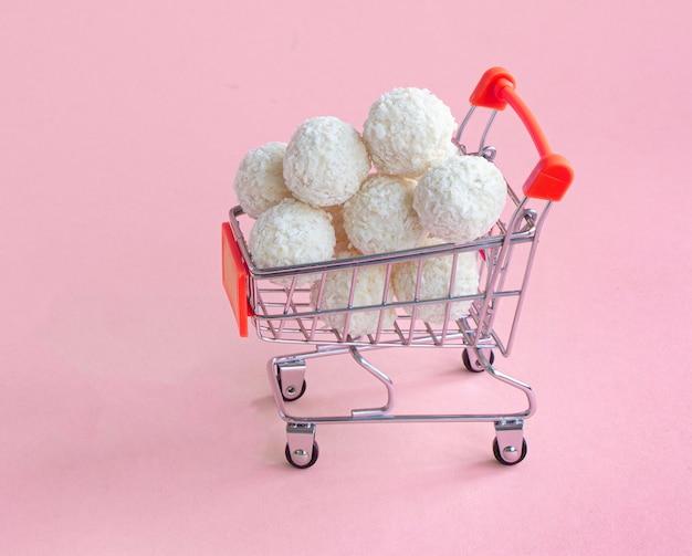 Kokosnoot ronde snoepjes in een mini-winkelmandje isoleren op een speldachtergrond supermarktwinkelconcept volle kar met snoep sweet