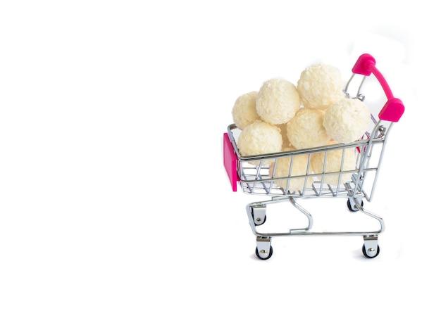 Kokosnoot ronde snoepjes in een mini-winkelmandje isoleren op een witte achtergrond supermarkt winkelconcept volle kar met snoep