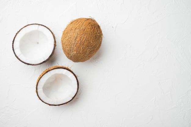 Kokosnoot snijdt gebroken set, op witte stenen tafelachtergrond, bovenaanzicht plat, met kopieerruimte voor tekst