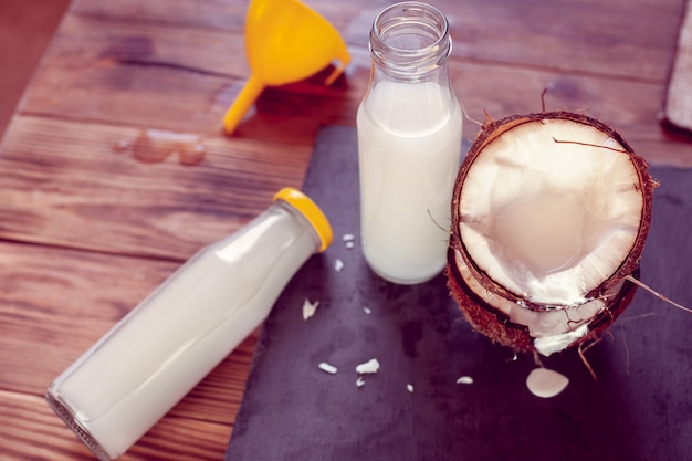 Kokosnoot, twee flessen met kokosmelk en trechter