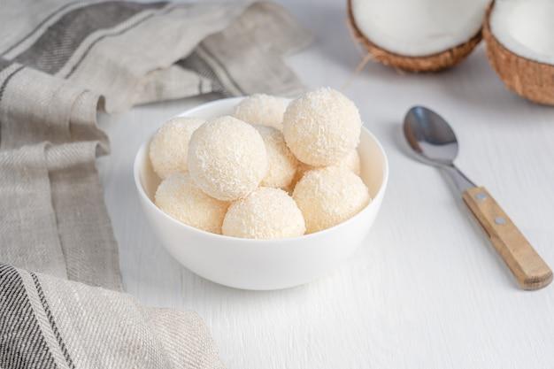 Kokosnoot zoete biologische truffels geserveerd in kom met lepel en textiel handdoek op witte houten tafel