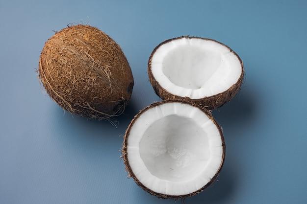Kokosnoothelften, kokosstukjes ingesteld, op blauwe getextureerde zomerachtergrond
