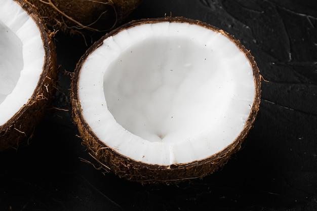 Kokosnoothelften, kokosstukjes set, op zwarte donkere stenen tafelachtergrond
