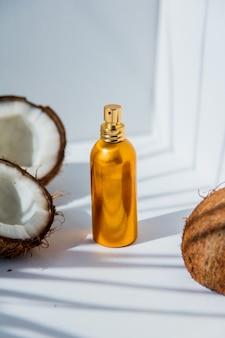 Kokosnoten en parfumfles op witte bacgkround met schaduwen