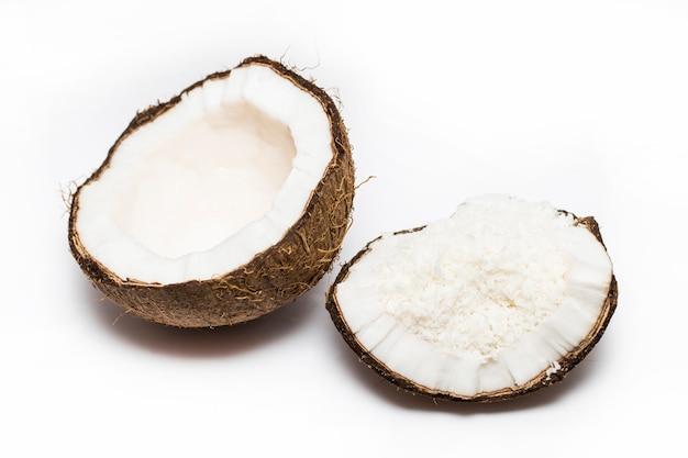 Kokosnoten met kokosnotenvlokken die op de witte achtergrond worden geïsoleerd