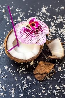 Kokosnoten met kokosnotenvlokken en orchidee op de grijze steenachtergrond
