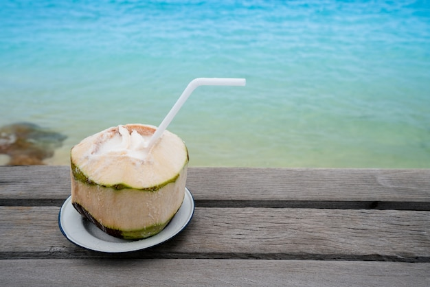 Kokosnotendrank op het het strandeiland van het zand oceaan