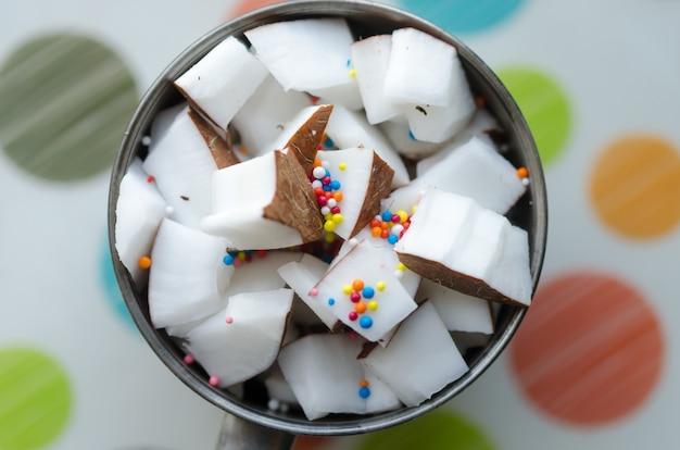 Kokosnotenkubussen met kleuren candys in een kom. macro foto.