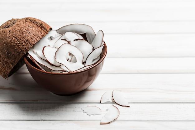 Kokosnotenspaanders in een bruine kom op witte houten