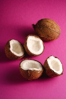 Kokosnotenvruchten op roze purpere trillende duidelijke achtergrond, abstract voedsel tropisch concept, hoekmening
