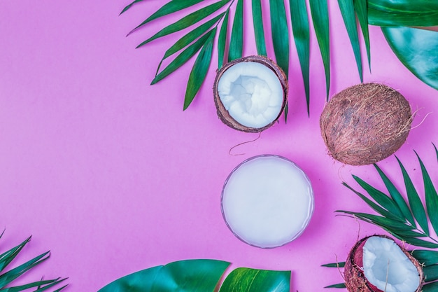 Kokosolie en kokosnoten met tropische bladeren