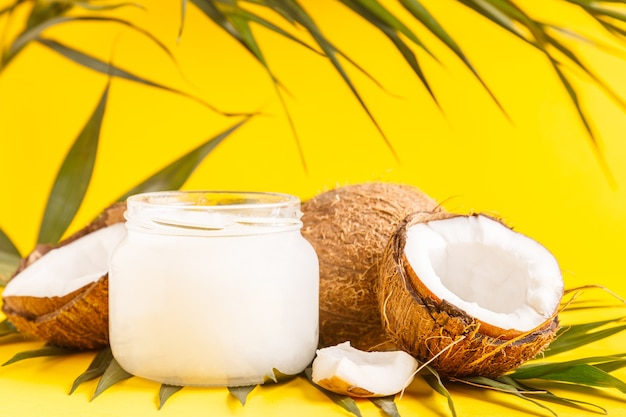 Kokosolie en kokosnoten op een achtergrond met tropische bladeren